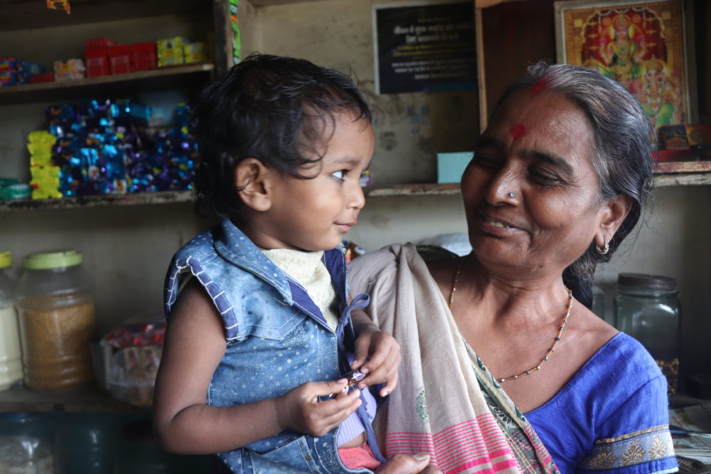 Street Vendor Basanti Jodha cares for her granddaughter inside the small shop that doubles as the family home in Indore, India