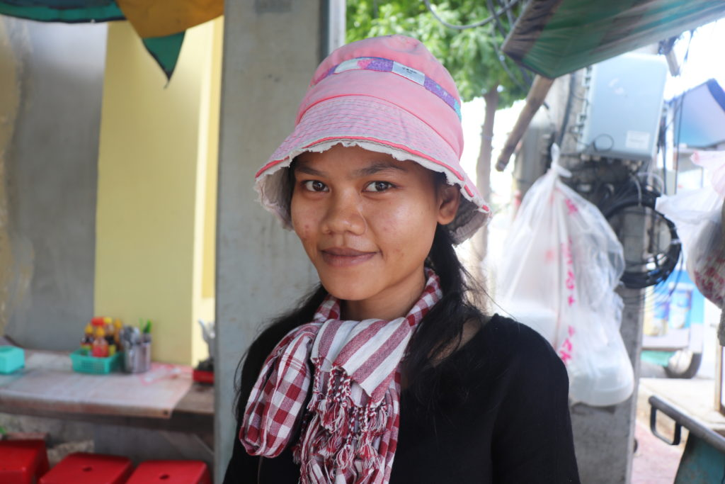 Sem Samol works at her drinks stall and her sister's food stall outside a television station in Phnom Penh, Cambodia