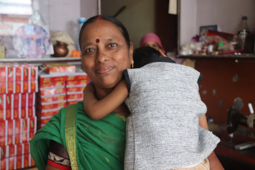 Sushila Rathore cares for her granddaughter in her home, which doubles as a shop in Indore, India.